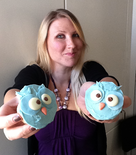 Tamlyn holds up 2 cupcakes - branded with our TLD owls